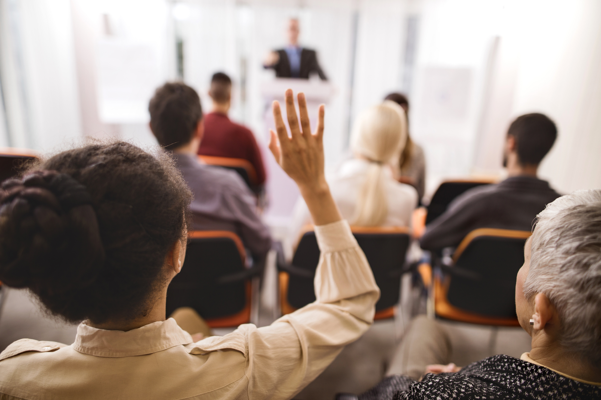 woman raising her hand to ask a question at a seminar or conference session