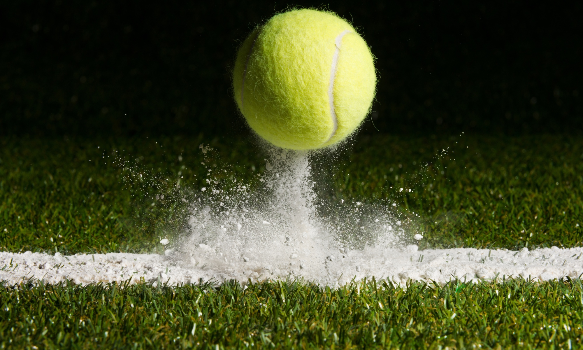 photo of tennis ball bouncing on a grass court